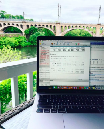Run a 15-Minute SEO Audit   KWSM Development   MacBook Pro with open windows on a table outside overlooking a bridge