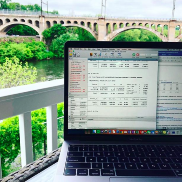 Run a 15-Minute SEO Audit | KWSM Development | MacBook Pro with open windows on a table outside overlooking a bridge